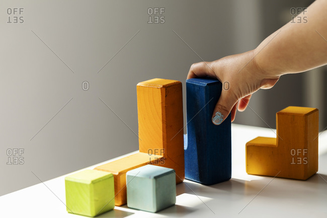 Girl playing with colorful building blocks at home