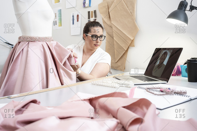 Seamstress working in tailor shop and presenting skirt via video call