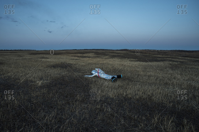 Boy wearing space suit lying on meadow in the evening