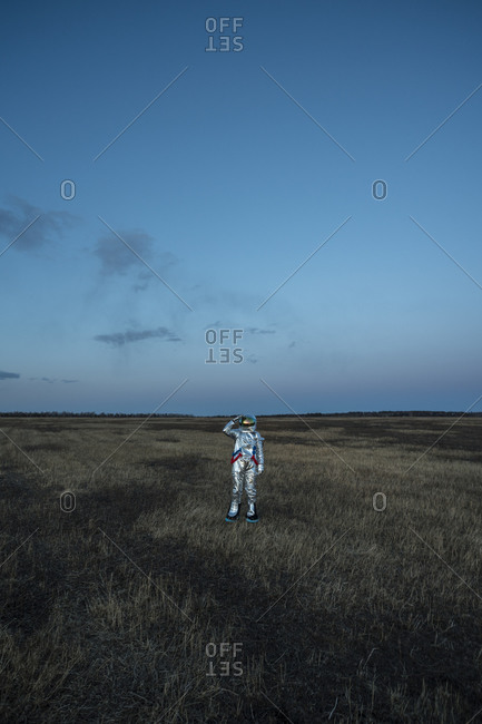 Spacewoman on meadow in the evening