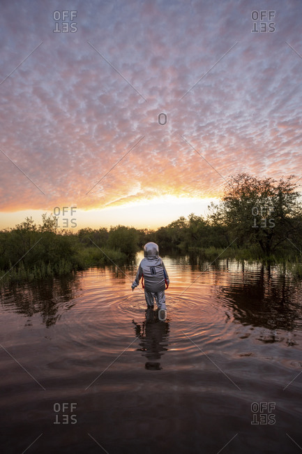 Spacewoman walking in water at sunset