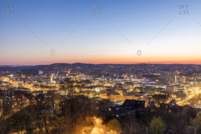 Germany- Baden-Wurttemberg- Stuttgart- Clear sky over illuminated city at dusk