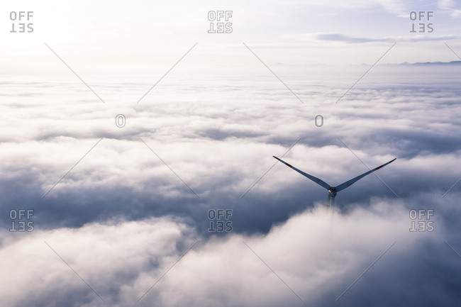 Germany- Aerial view of wind turbine shrouded in clouds at dawn