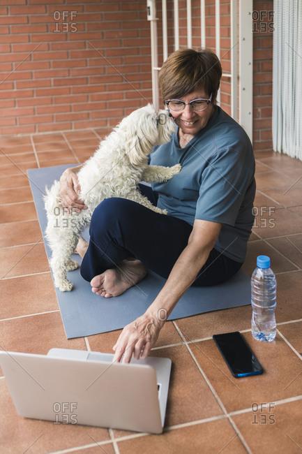 Sportive senior woman using laptop on balcony- dog kissing her