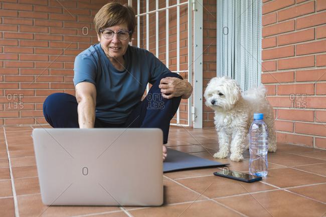 Sportive senior woman using laptop on balcony