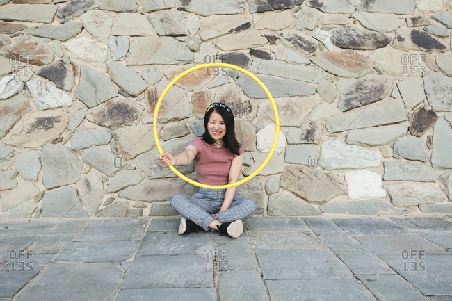 Happy woman with hula hoop in front of a wall