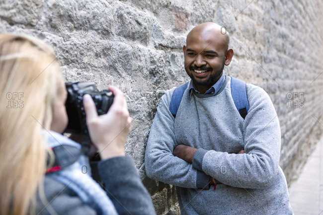 Woman taking photo of her smiling boyfriend with camera- Barcelona- Spain