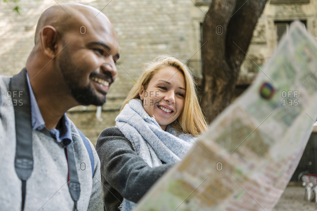 Portrait of happy woman looking at city map together with her boyfriend- Barcelona- Spain