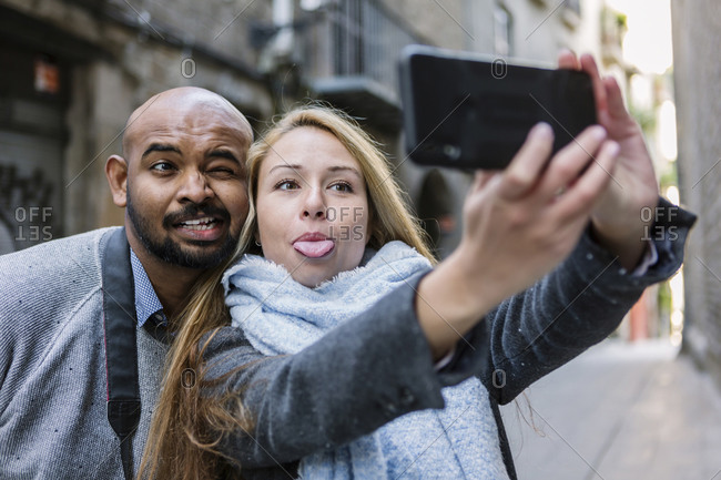 Portrait of couple pulling faces while taking selfie with smartphone- Barcelona- Spain