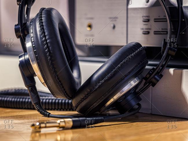 Black Hi-Fi headphones with a gold input jack on a wooden floor
