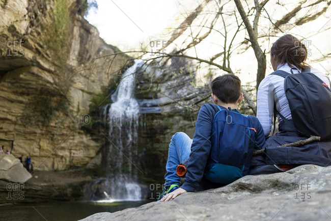 Back view of two young teenagers sitting on rock against waterfall
