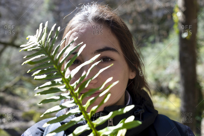 Portrait of a hispanic woman behind leaves outdoors in a forest