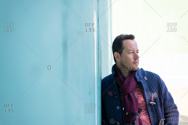 Bearded man in casual clothes leaning on green wall while looking away outdoors