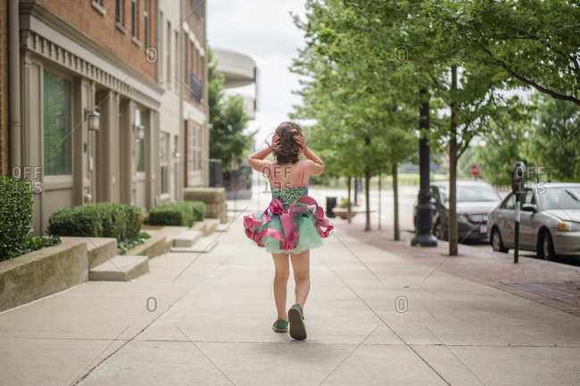 A small girl walks down sidewalk in tutu holding hair against wind