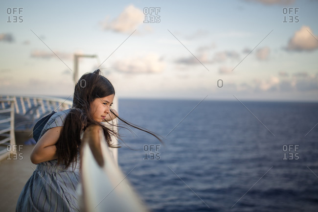 A young girl leans against a ship railing at sunset gazing at ocean