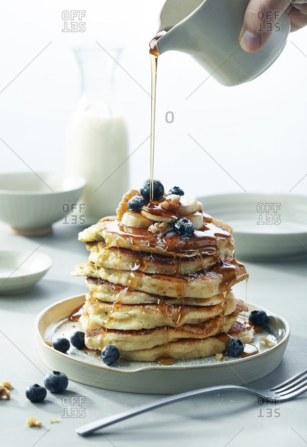 Stack of Blueberry Banana Walnut pancakes with Syrup Pouring Breakfast