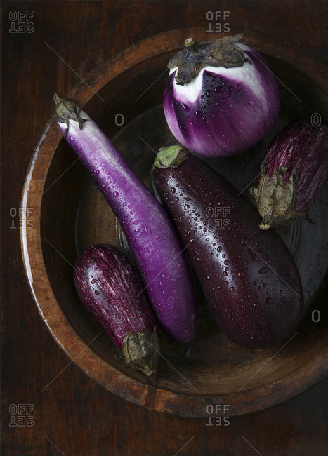 Eggplants in Wooden Bowl Wet with Droplets