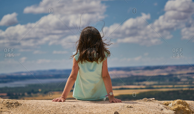 Girl sitting on her back in landscape and blue sky with white clouds