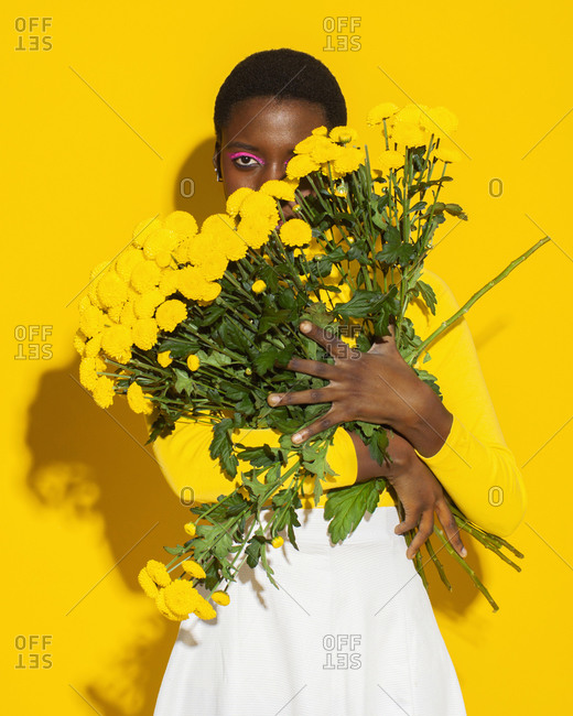 Sensual woman with yellow flowers, total yellow