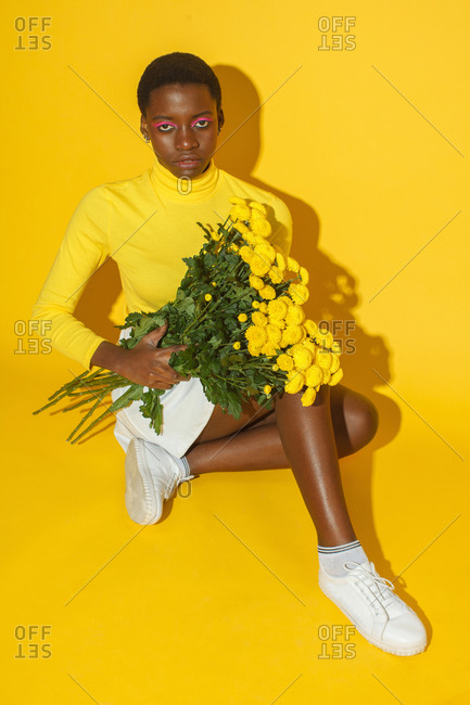 Young woman with yellow flowers, total yellow