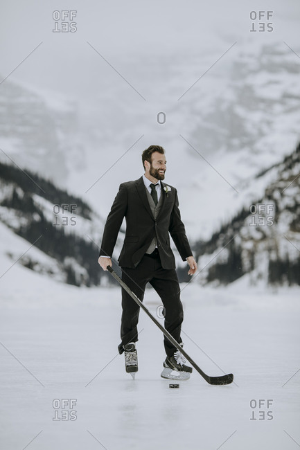 Man in black suit, hockey skates and hockey stick poses on frozen lake