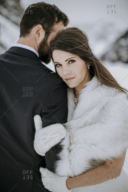 Bride in wedding dress and fur rests head against groom in winter