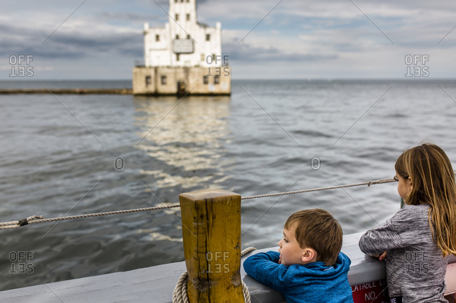 Children Looking at Lighthouse on Cloudy Day