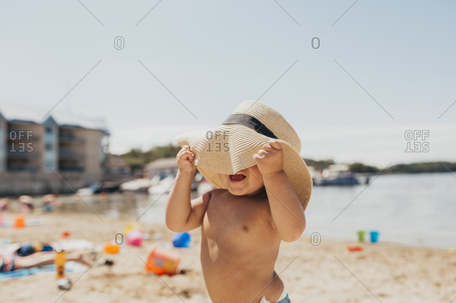 Toddler Boy Playing Peek-a-boo with Sun Hat on Beach