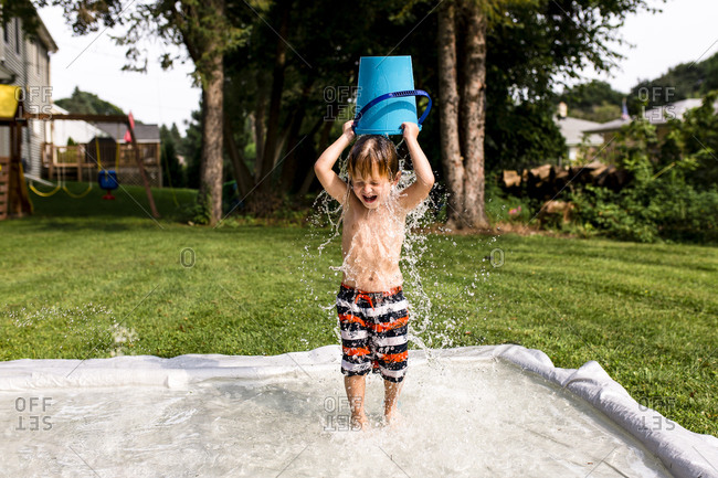 Young Boy Pouring Water Bucket Over Head
