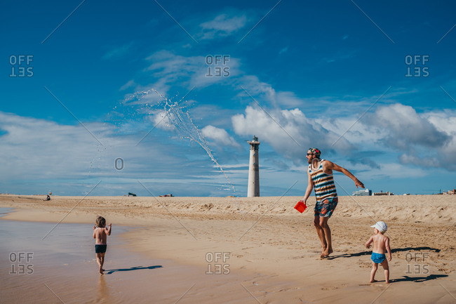 Kids playing with water at the beach with their dad on a sunny day