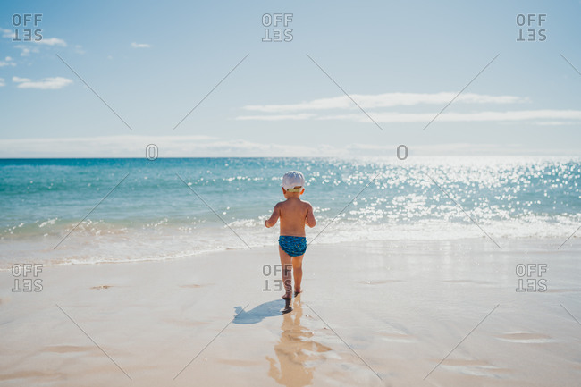 Boy walking into the water at the beach on a sunny day on vacation
