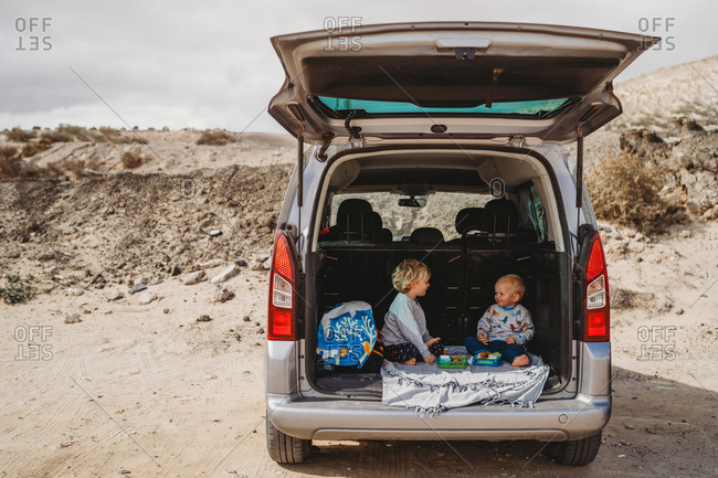 Kids having a picnic in the trunk of their car during vacation holiday