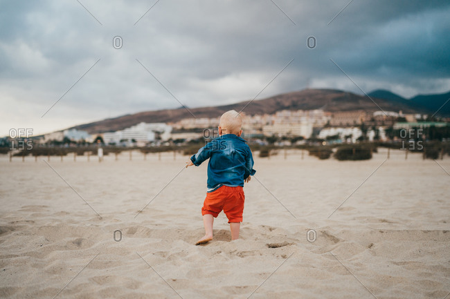 Boy playing at the beach on a cloudy and cold day