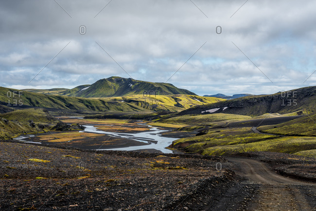 Black dirt road winding through green landscape in Iceland