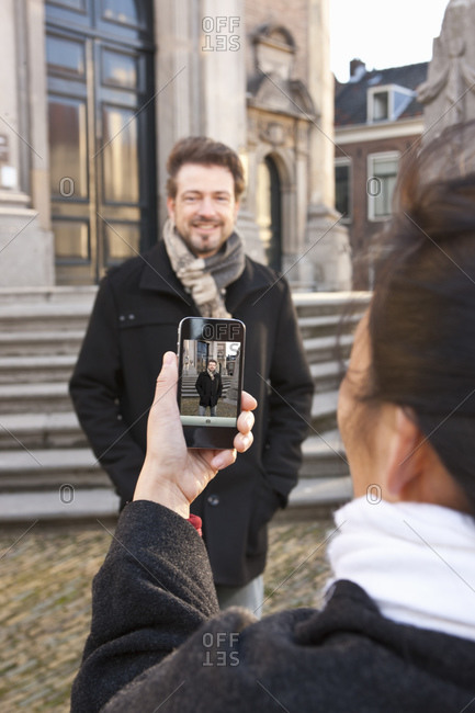 Woman taking picture of man with smartphone in Middelburg