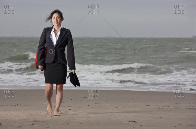 Business woman walking on empty beach holding her shoes
