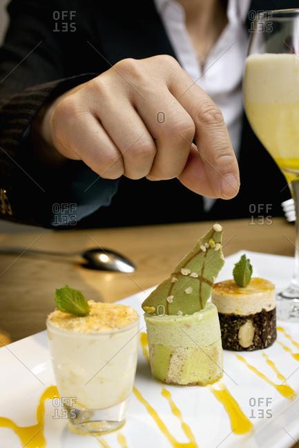 Businesswoman reaching for dessert at luxury hotel restaurant