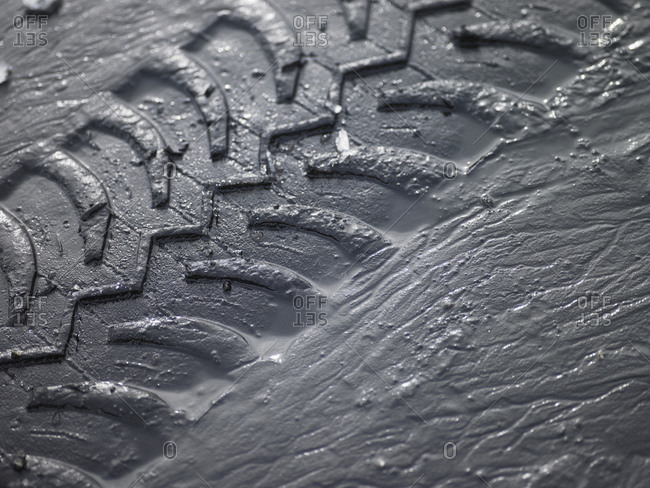 Close up of SUV tire tracks in grey mud