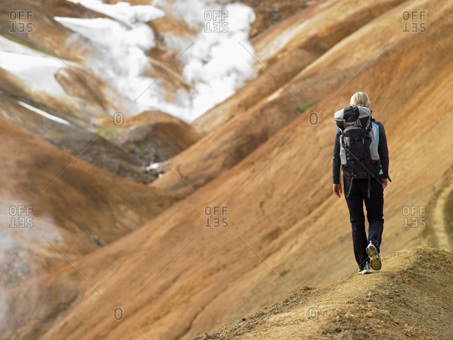 Young woman hiking along ridge in the Icelandic highlands