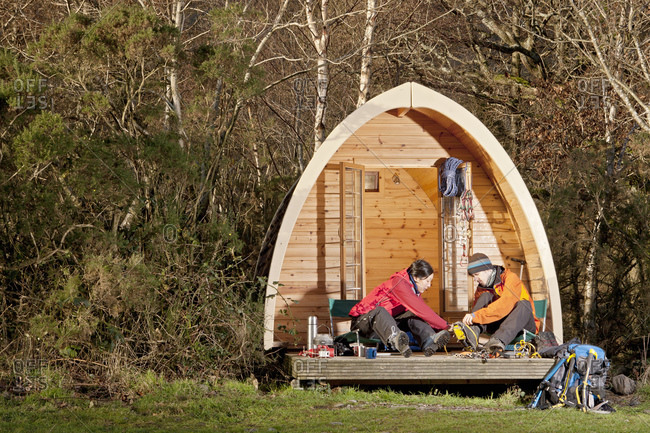 Couple preparing for a hike in front of camping pod in the UK