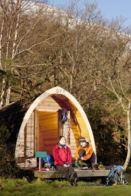 Couple getting ready for a hike in front of camping pod