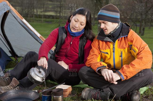 Couple preparing hot beverage at campsite in the UK