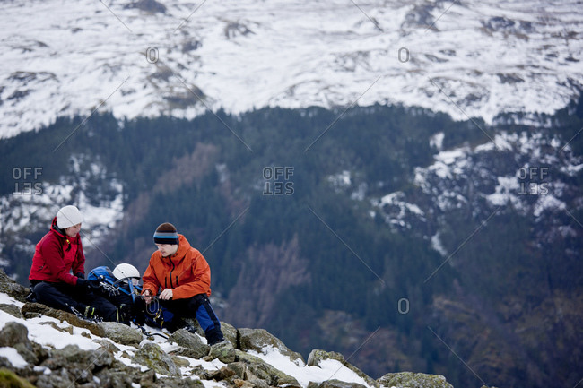 Couple resting on the way up Helvellyn mountain in the Lake District