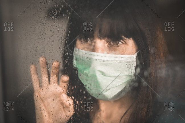 A young girl wearing a mask in the Covid-19 pandemic with her hand on the window