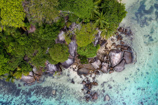 Aerial view of the granitic boulders along the crystal clear island of Ile Moyenne, Sainte-Anne National Marine Park, Seychelles