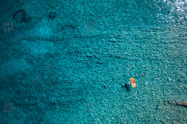 Aerial view of a woman swimming in the turquoise waters of Stara Baska, Croatia
