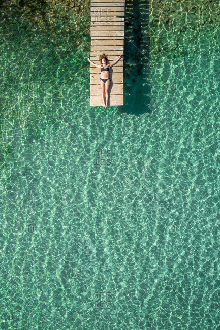 Vis, Croatia - 13 SEPTEMBER 2019: Aerial view of a woman on a pier at Stoncica beach