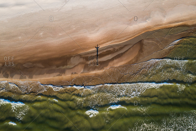 Aerial view of person silhouette shadow standing on Baltic sea shore beach in Klaipeda, Lithuania. Perspective of beautiful nature patterns on surface.