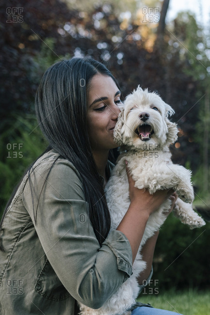 Young woman hugging her dog with feeling