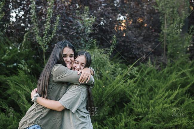 Teenage girls hug happily outside